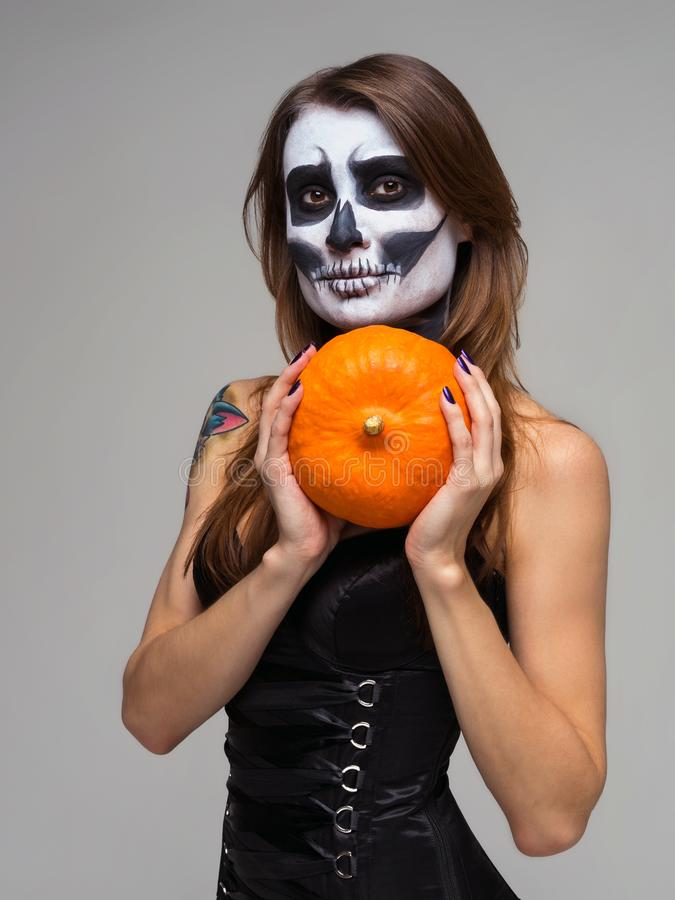 Portrait of woman with halloween skeleton makeup holding pumpkin over gray background royalty free stock image