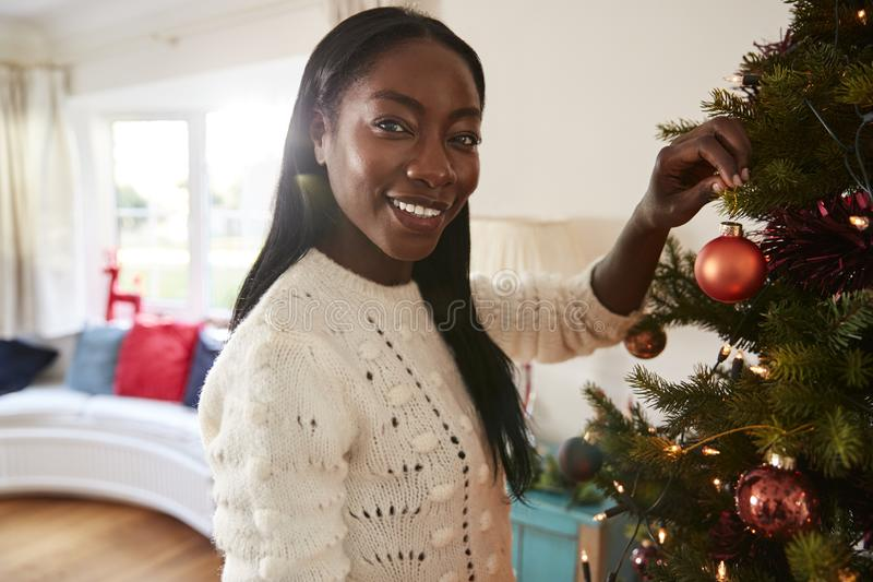 Portrait Of Woman Hanging Decorations On Christmas Tree At Home stock photo