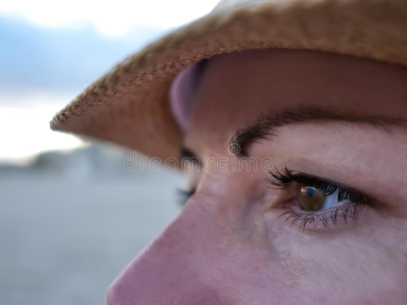 Portrait of a young woman in a hat looking to the side, close-up stock photo
