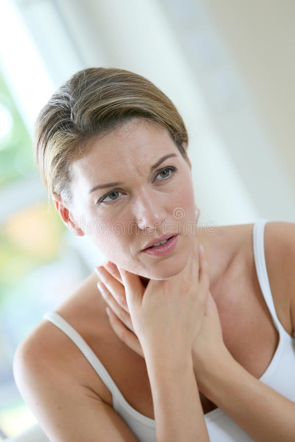 Portrait of a woman having a cold. Middle-aged woman having a cold and coughing stock photo