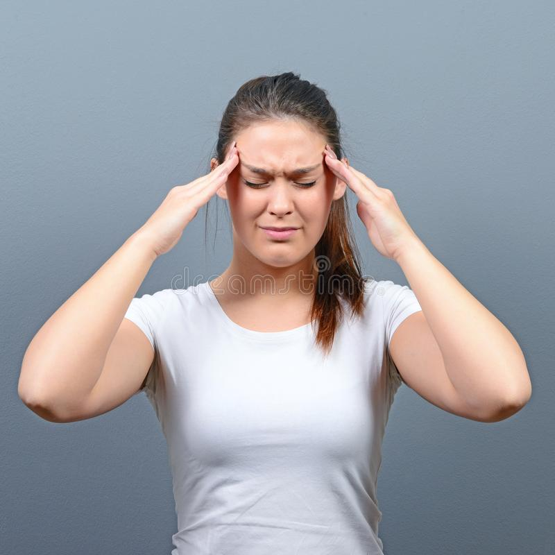 Portrait of woman with headache against gray background royalty free stock photography