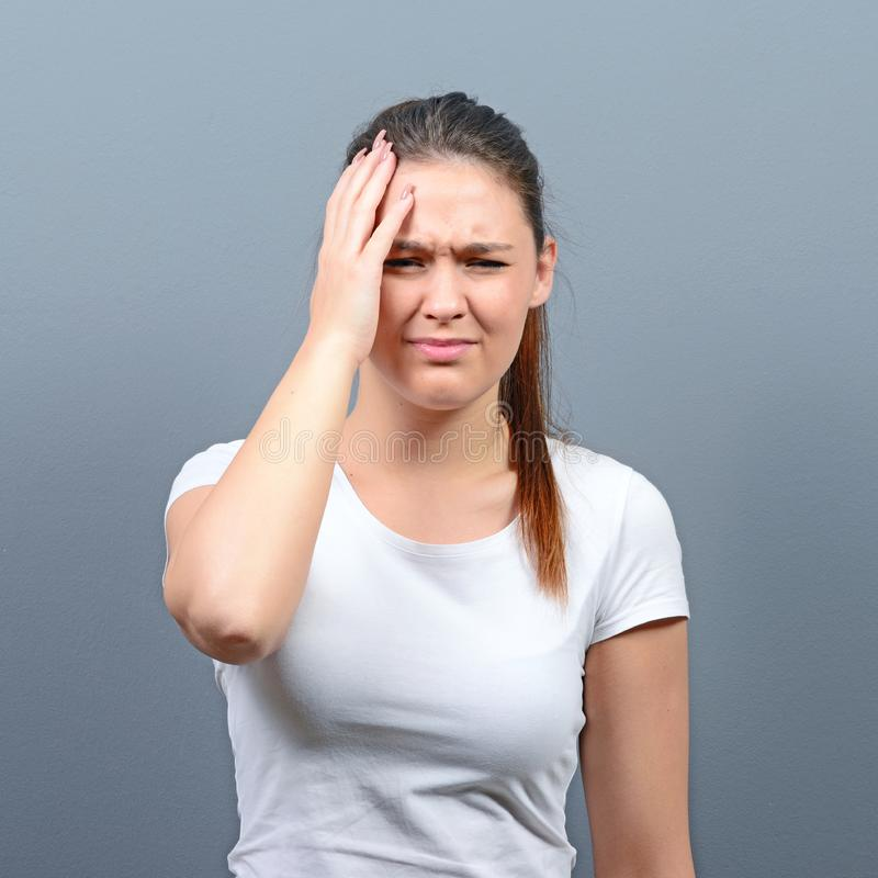 Portrait of woman with headache against gray background stock photo