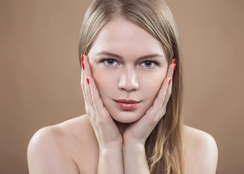 Portrait of a woman holding a hand by her face. She has daytime make-up, excellent skin, neat red nails and long blond hair. stock image