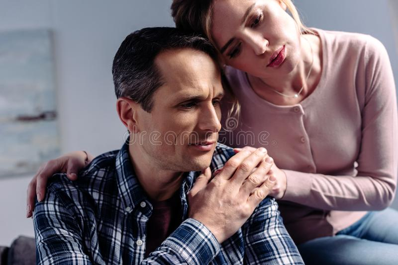 Portrait of woman hugging sad man that sitting on sofa. At home stock photography