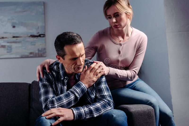 Portrait of woman hugging sad man that sitting on sofa. At home stock image
