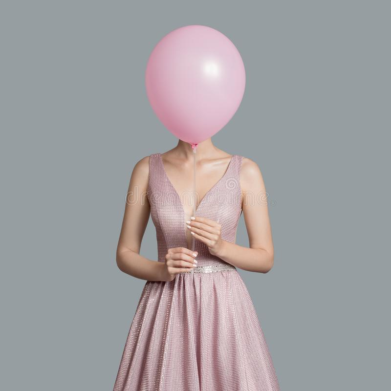 woman im evening dress. Hides her face behind pink balloon stock photos
