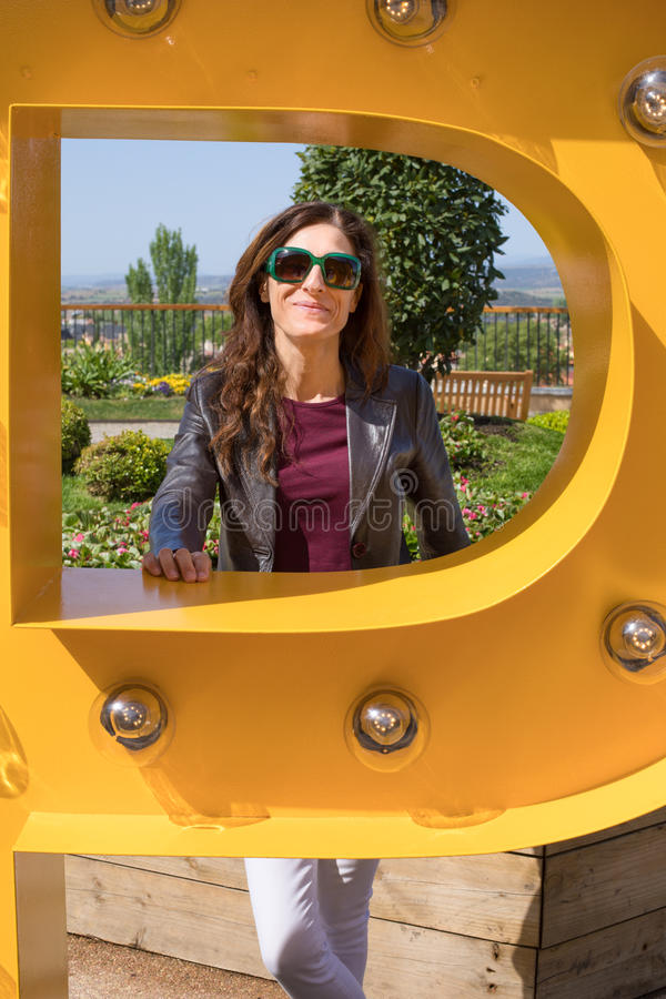 Portrait of woman inside yellow big metal letter royalty free stock images