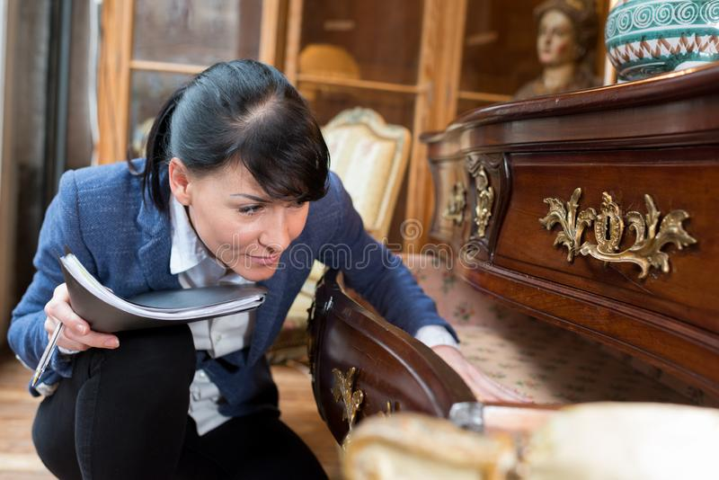Portrait woman inspecting furniture in antique store royalty free stock photography