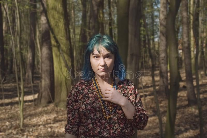Portrait of a woman with an interesting appearance walking in the woods. Portrait of a woman in blue hair with an interesting appearance walking in the woods stock images