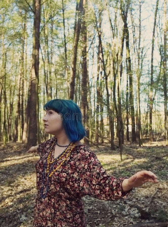 Portrait of a woman with an interesting appearance walking in the woods. Portrait of a woman in blue hair with an interesting appearance walking in the woods stock photo