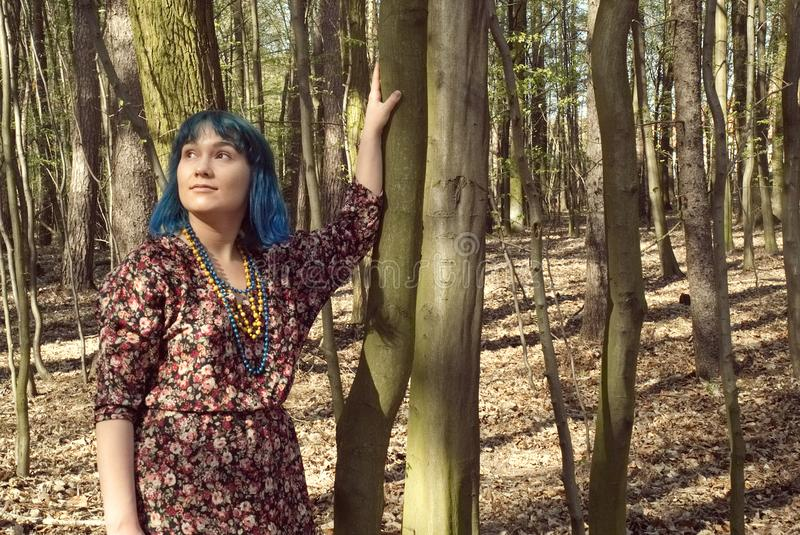 Portrait of a woman with an interesting appearance walking in the woods. Portrait of a woman in blue hair with an interesting appearance walking in the woods royalty free stock photo
