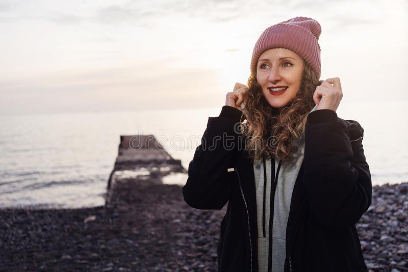 Portrait of woman in jacket and hat standing on beach at sunset. Girl in sportswear walks in evening along seashore. Portrait of a woman in a jacket and hat royalty free stock images