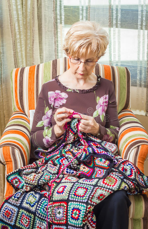 Portrait of woman knitting a vintage wool quilt royalty free stock photography