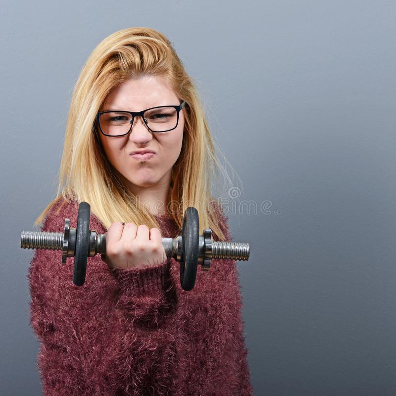 Portrait of woman lifting weights against gray background royalty free stock photos