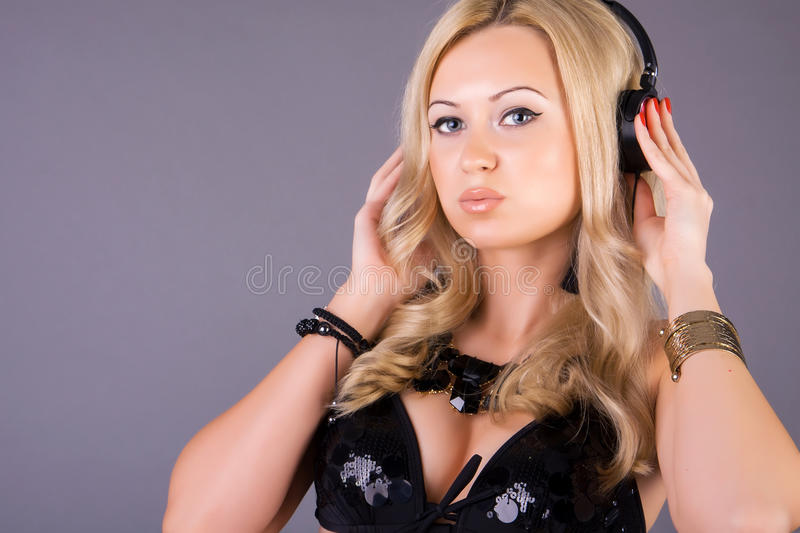 Portrait of a woman listening to music. Portrait of a young woman with headphones over grey background stock photo