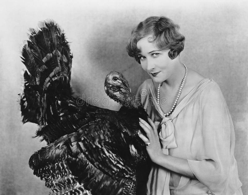 Portrait of woman with live turkey. (All persons depicted are no longer living and no estate exists. Supplier grants that there will be no model release issues royalty free stock photography