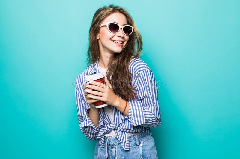 Portrait of young woman looking aside while drinking takeaway coffee or tea from paper cup isolated over blue background royalty free stock photos