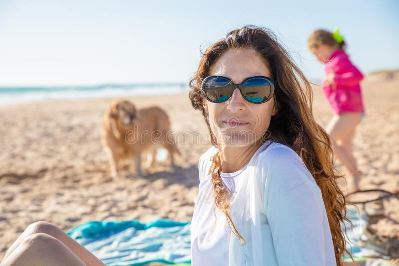 Portrait of woman looking at in beach with her daughter and dog royalty free stock photography