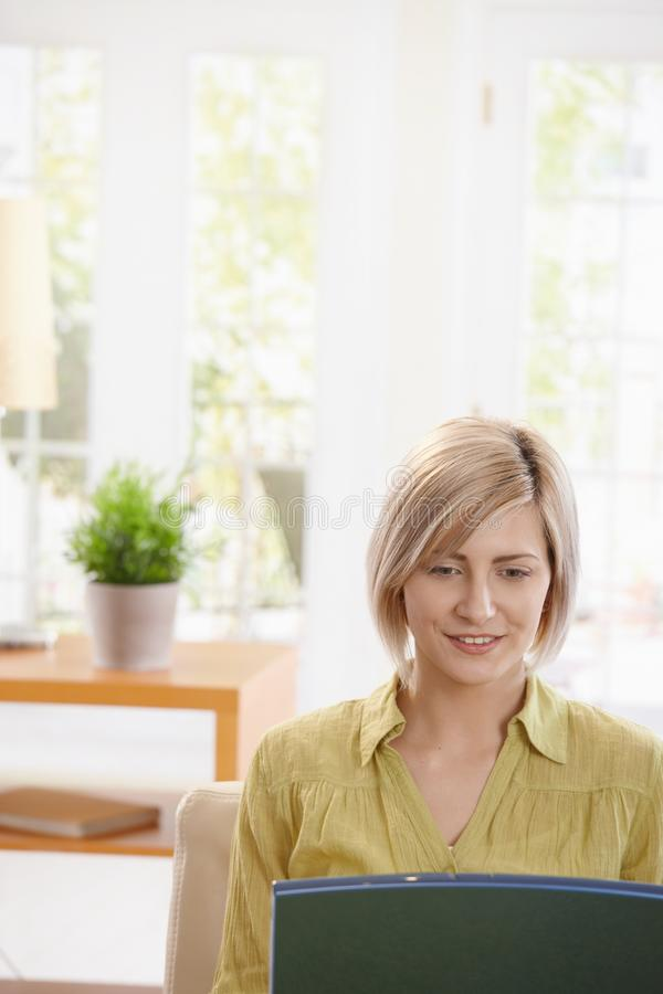 Portrait of woman looking at laptop. Computer sitting on sofa at home, smiling stock photo