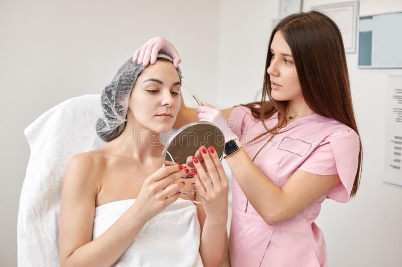 Portrait of woman looking in mirror at cosmetologist cabinet, cosmetologist examines her client, attractive female after anti royalty free stock photo