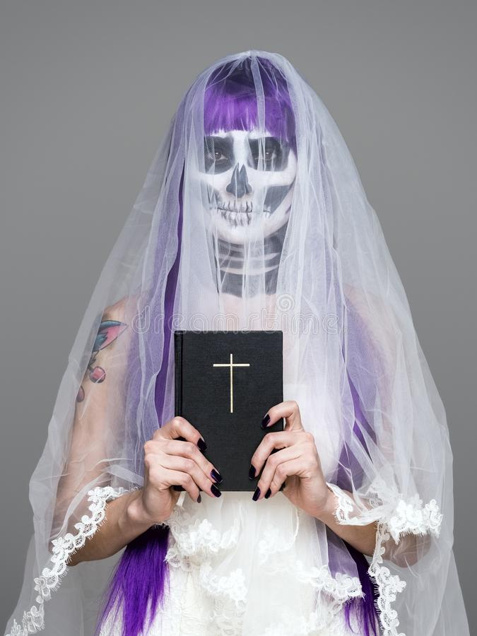 Portrait of woman looks at the camera with terrifying halloween skeleton makeup and purple wig bridal veil, wedding dress, holds t royalty free stock photo