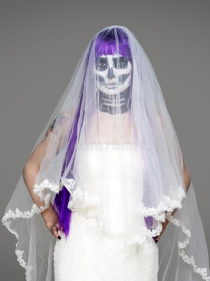 Portrait of woman looks at the camera with terrifying halloween skeleton makeup and purple wig bridal veil, wedding dress over gra stock image