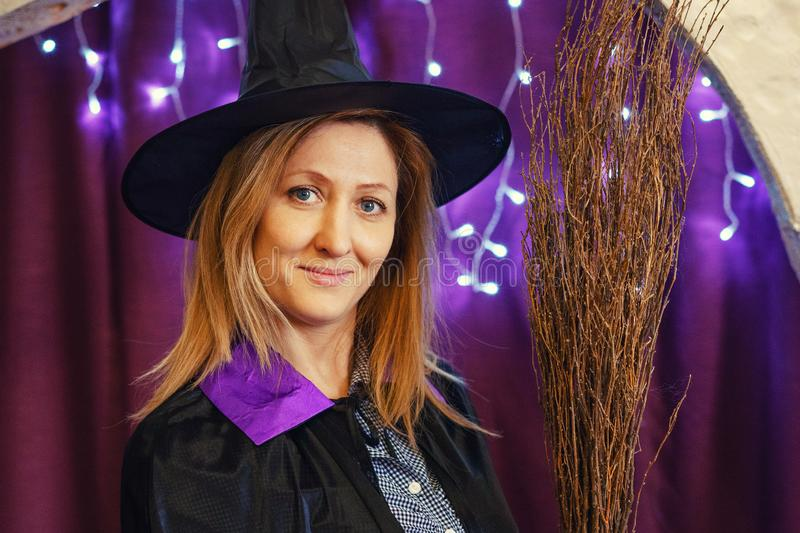 Portrait of a woman in a magician`s hat with a broom on a bokeh background, Halloween concept.  royalty free stock photos