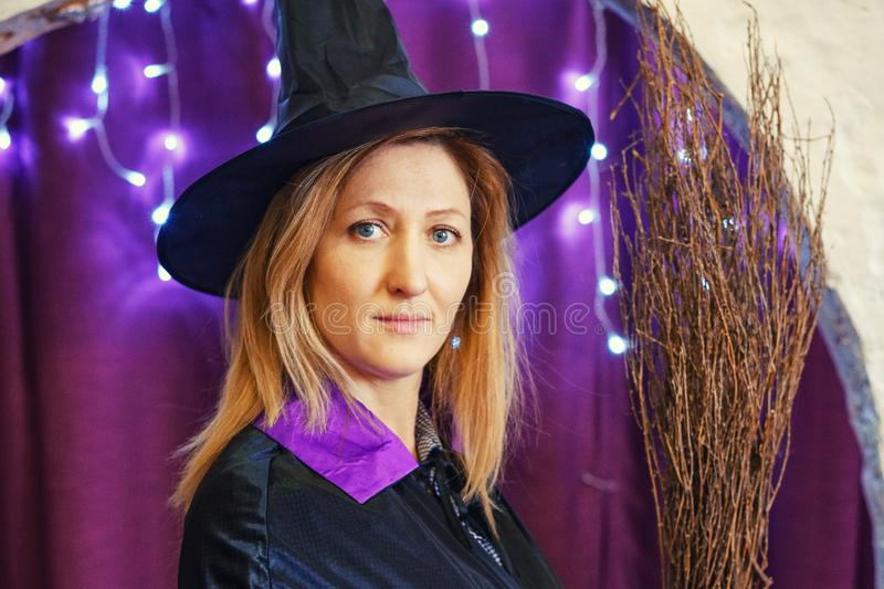 Portrait of a woman in a magician`s hat with a broom on a bokeh background, Halloween concept.  royalty free stock photo