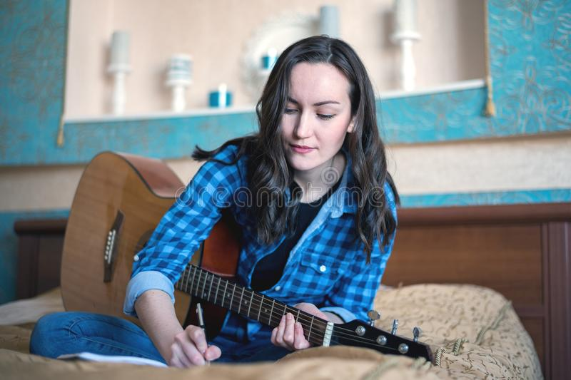 Portrait of a woman make music with an acoustic guitar writing ideas in a notebook royalty free stock images