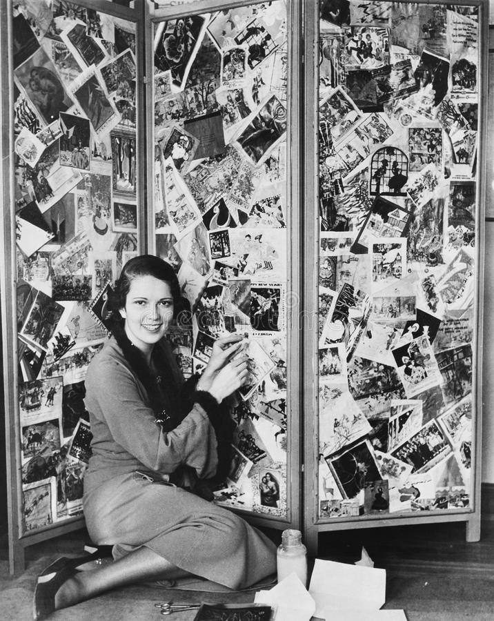 Portrait of woman making Christmas card collage on screen royalty free stock photography