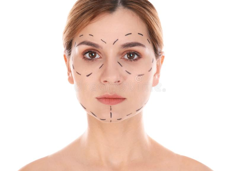 Portrait of woman with marks on face for cosmetic surgery operation against white royalty free stock photography