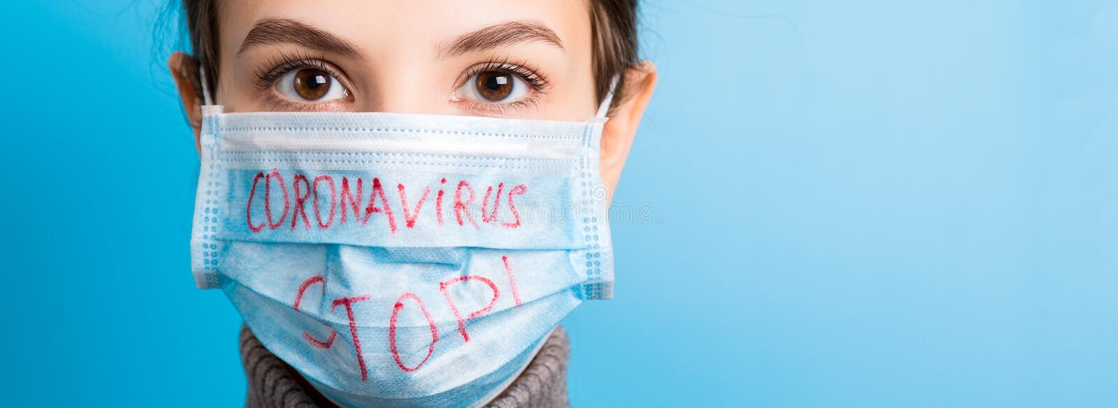 Portrait of a woman in medical mask with stop text at blue background. concept. Respiratory protection.  stock photography