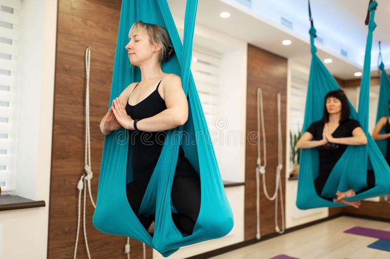 Portrait of Woman meditation in hammock. fly yoga stretching exercises in gym. Fit and wellness lifestyle royalty free stock photography
