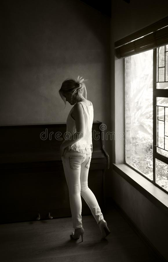 Portrait of woman in monochrome posing next to a window royalty free stock photos