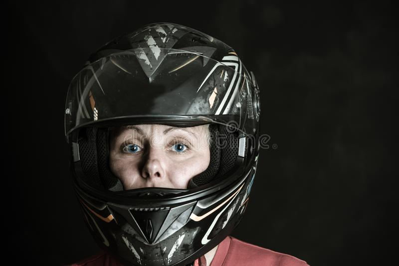 Danger and adrenaline are my name - portrait of a woman in a motorcycle helmet. Portrait of a woman in a motorcycle helmet, danger and adrenaline are my name stock photo