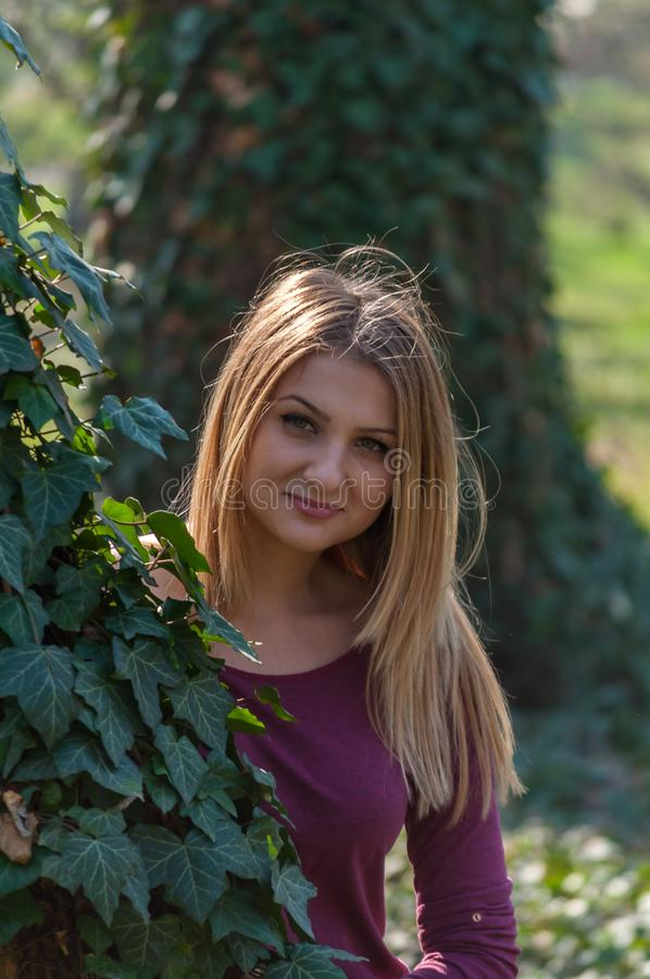 Portrait of a woman. Outdoors portrait of a woman, hiding in branches of ivy royalty free stock images