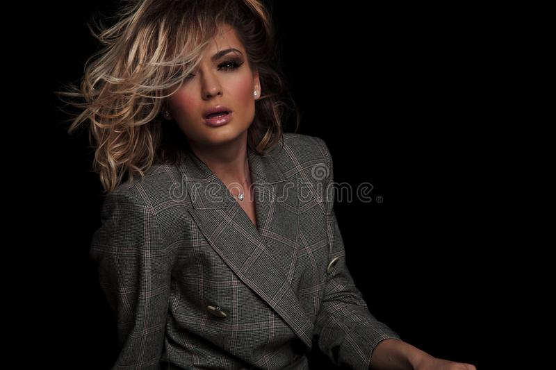Portrait of woman with parted lips and messy blonde haor. Portrait of beautiful woman with parted lips and messy blonde hair sitting on black background while stock photos