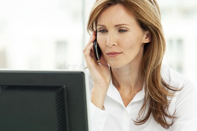 Woman on the phone - businesswoman using phone in office - corporate executive. Portrait of a woman on the phone - businesswoman using smartphone in office royalty free stock photography