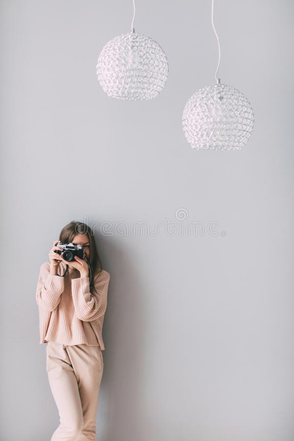 Portrait woman photographer covering her face with camera at home. royalty free stock photo