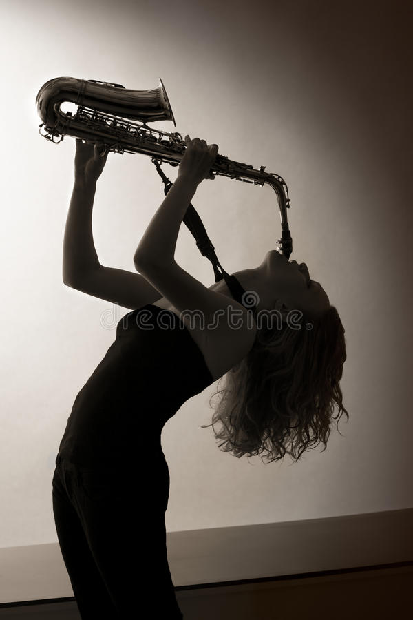 Portrait of woman playing saxophone, sepia toned. royalty free stock photo