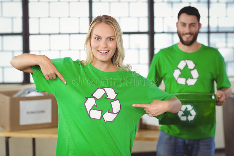 Portrait of woman pointing towards recycling symbol on tshirts. Portrait of women pointing towards recycling symbol on tshirts with colleague in background stock photo