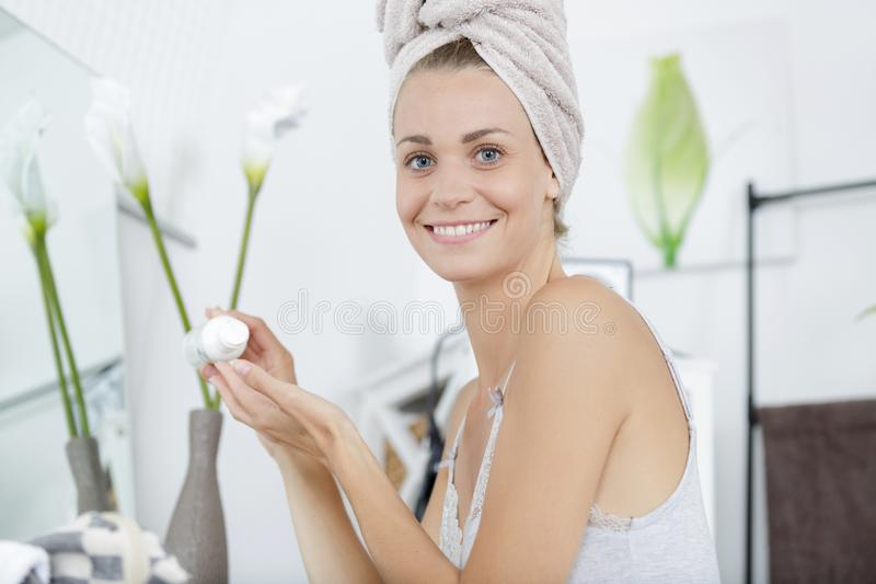 Portrait woman putting cream on face royalty free stock image