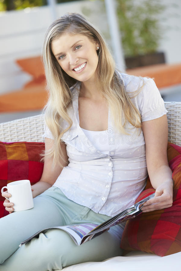 Portrait Of Woman Reading Magazine On Outdoor Seat royalty free stock photo