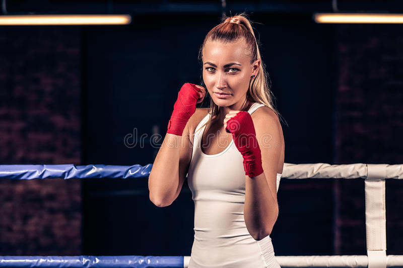 Portrait of woman with red boxing bandage on hands in gym royalty free stock images