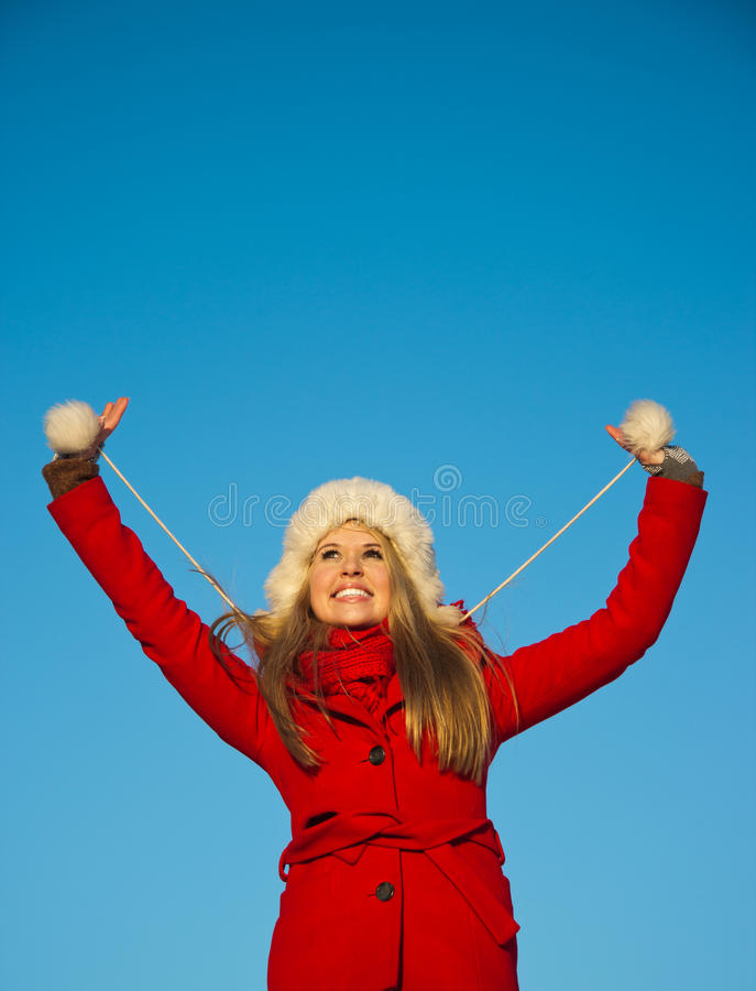 Portrait of woman in red coat blue backgound. Playful portrait of young blond woman in red winter coat holding hands up stock image