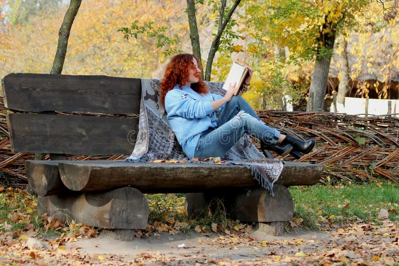 Beautiful Woman with red hair in the autumn park. sits on a bench and reads a book. Autumn background. Nearby is a warm blanket wi stock photos