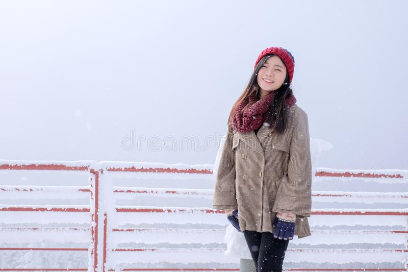 Portrait of woman with red wool. Hat feeling very happy and cold under snowy weather at Shin-hotaka observation deck, Japan Alps stock image