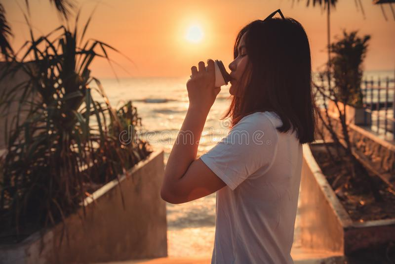 Portrait of Woman is Relaxing at The Beach Duration Summer While Coffee Drinking, Silhouette of Asian Tourist Relaxation in stock image