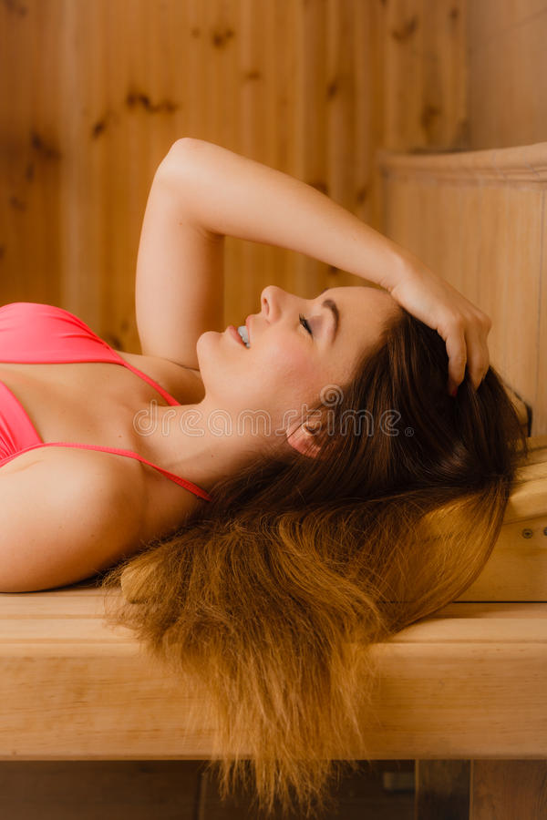 Portrait of woman relaxing in sauna. Spa wellbeing. Portrait of young woman relaxing in wooden finnish sauna. Attractive girl in bikini resting. Spa wellbeing stock photos