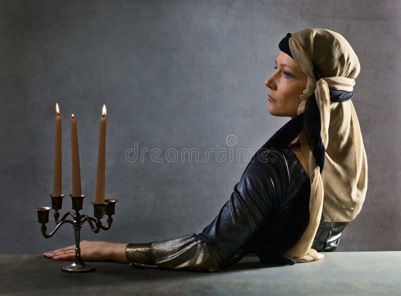 Portrait of woman in Renaissance dress. Portrait of woman with candlestick in Renaissance dress royalty free stock image